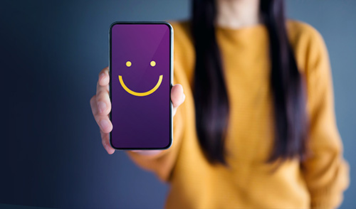 Woman holding a Smartphone with a smiley face