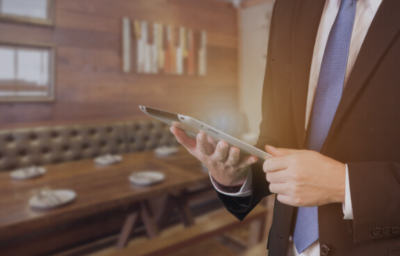 Man in hospitality looking at a digital tablet